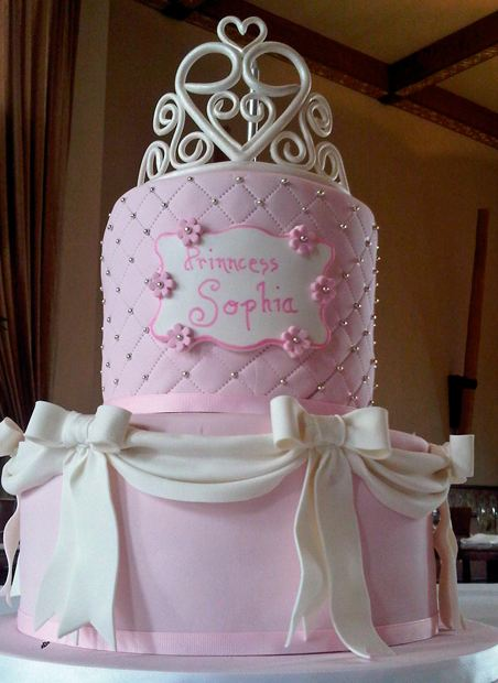 Two tier pink birthday cake with white bows for girl